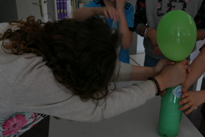 Ballon de baudruche gonflé sur une bouteille en plastique et tenu par une fille au visage caché par ses cheveux